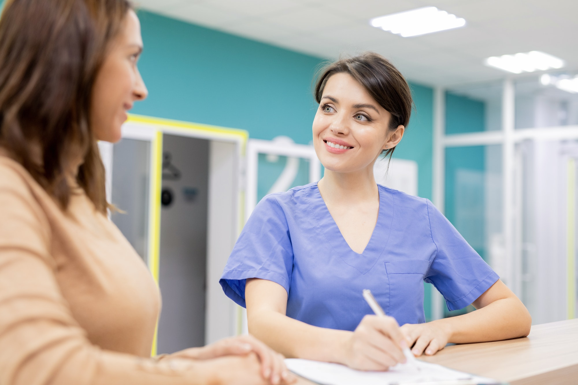 Doctor in uniform smiling at patient while consulting young woman in clinics